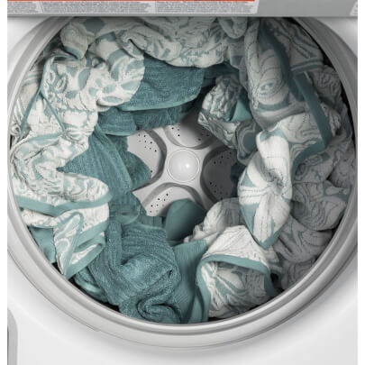 Interior view with wet clothes in the white GE top load washer with 4.6 cubic foot capacity- GTW500ASNWS